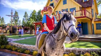 Pippi Långstrump på sin häst Lilla Gubben framför nybyggda Villa Villekulla i Astrid Lindgrens Värld.