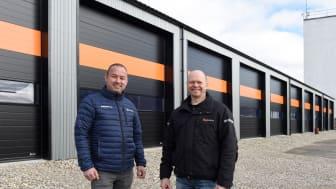 HPH Totalbyg har opført Djurs Kloakservices nye bygninger, og Lindab har leveret en helt særlig port med orange striber. Anders Godsk fra Lindab (tv.) og byggeleder Palle Simonsen fra HPH Totalbyg (th.)
