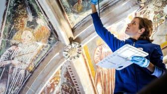 Woman restoring ceiling paintings