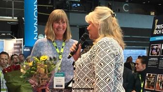 Karin Goddard, HR-Chef Riksbyggen tar emot blommor och diplom från Mona Finnström, vd Fastigo.