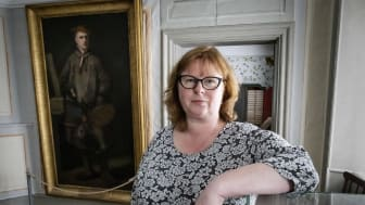 Annika Windahl Pontén standing in front of a portrait of Carl Linnaeus.