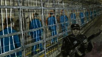 276367_Detainees walking through a narrow fenced enclosure in an internment camp in Xinjiang_ China.jpg