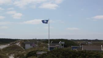 Bilden visar badhytterna vid Skanörs havsbad med den blå flaggan hissad.