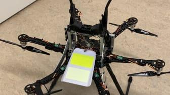 Nedre bild: En drönare som ska flyga upp och montera en fågelavvisare (gul) på en ledning. Övre bild: Monterad fågelavvisare på ledning.