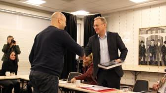Raymond Johansen på besøk i Bydel Sagene. Her får han boken Livet langs elva av bydelsutvalgsleder Helge Stoltenberg (Foto: Boligbygg)