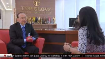Dr Lim Wee Chai gives an interview with his product shown prominently on his right hand