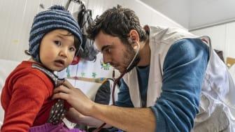 Läkaren Leonidas Alexakis undersöker ett barn på Läkare Utan Gränsers barnklinik på den grekiska ön Lesbos. Foto: Anna Pantelia/Läkare Utan Gränser