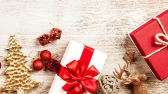 Julklappar och juldetaljer på träbord.