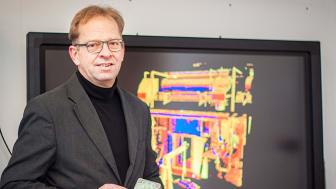 """Stefan Seipel med en """"range camera"""" som mäter en 3D bild. Bilden på skärmen i bakgrund är en 3D laserskannad del av en industriell facilitet."""