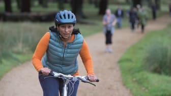 A woman cycles through a park