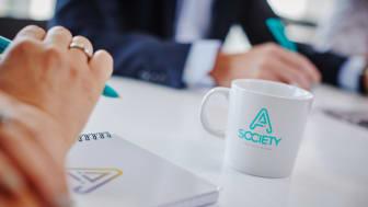 A Society information, kaffekopp, block och penna.