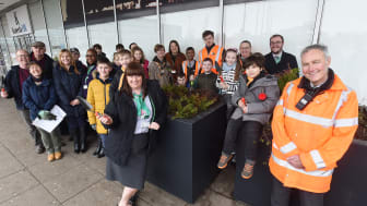 Railway staff, volunteers and local children gather at Milton Keynes station to fill new planters outside the station entrance