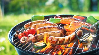 Korv och grönsaker grillas på kolgrill.