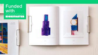 Magazine Wall Hanger WIDE med ett konstmagasin, på bordet ligger Original-modellen