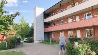 Lenny Petersson, ordförande i Brf Mönsteråshus 1, framför ett av föreningens hus som numera har en utanpåliggande hiss.