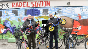 Manfred Heidemann von der Radlwerkstatt in der Bayernkaserne (l.), und Klaus Kickermann, Innere Mission München, freuen sich über die Radlspende der Stadtsparkasse München.