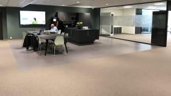 Kjøkkenområde og møteplass med muligheter for å kjøre presentasjoner på storskjerm.