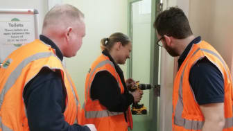 Natalie Parker repairing a toilet door at Worthing station in her first week