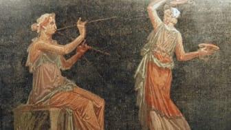 Kvinnliga musiker spelar på tibiae och cymbaler