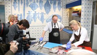 Fiskeriminister Per Sandberg og stjernekokken Cornelia Poletto viser hvordan man skal filetere en skrei.