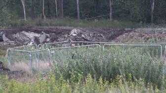 Området för den planerade reningsdammen består av lera och gyttja. Platsen där en grävmaskin sjönk och välte är inhägnad med byggstängsel. Bild tagen med teleobjektiv eftersom kyrkogårdsförvaltningen inte tillåter fotografering inne i arbetsområdet.