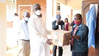 Senga Nsese, servicetekniker, lämnar över tester från Sverige till Panzisjukhusets chefsläkare Denis Mukwege.  Foto: Läkarmissionen
