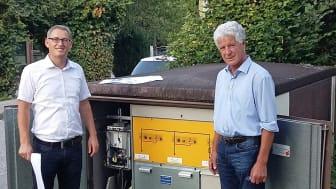 """Start für das """"Strom-Internet"""": Bad Feilnbachs Bürgermeister Hans Hofer (r.) und Bayernwerk-Netzbauleiter Gazmend Kryeziu vor einer für den Breitband-Powerline-Test umgerüsteten Trafostation."""