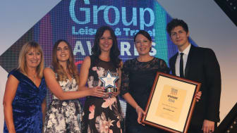 (L-R) Maureen Quinn of 'Just for Groups!' presents Sophie Thomas, Sales Executive – Groups, Hayley Walker, Sales Assistant – Groups and Ellie Fulcher, Sales Manager – Groups with the trophy alongside special guest and co-host, Magician Ben Hanlin.