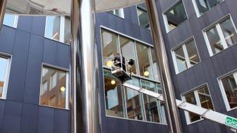 """Vinduespolerer fra TJEK Ejendomsservice, som er en del af Forenede Service, i gang med polere nogle af de mange glasflader på Professionshøjskolen UCC's 57.000 kvadratmeter store bygning i Carlsberg Byen i København kaldet """"Carlsberg Campus""""."""