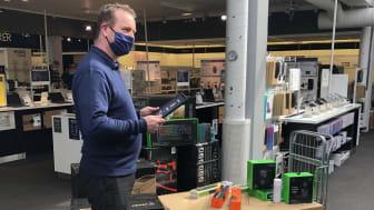 """Stolt varehussjef: Tom Lund smiler bak munnbindet idet han sammen med kolleger deler ut midler til """"Ung Arena"""" i Ulsteinvik. Foto: Elkjøp Norge"""