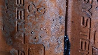 Undersiden af et tag med betontagsten, der er understrøget med sort fugemasse. Her kan man tydeligt se, hvordan kondensdannelserne har samlet sig i dråber på tagstenens underside.