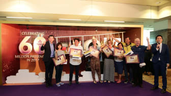 CAG's Chief Executive Officer, Mr Lee Seow Hiang (first from left) and Scoot's Chief Operating Officer, Mr Ng Chee Keong (third from right), with the six lucky passengers who joined Changi Airport's 60 millionth passenger celebrations