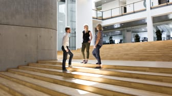 Ditte Brix (i midten) taler med kollegerne på trappen i det store atrium.