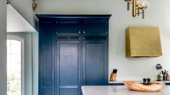 Pladsen i det højloftede køkken er udnyttet optimalt med højskabe. Fasede fodlister, paneler og hulkehllister, der kan bestilles i metermål, er i hele køkkenet anvendt til at fundende indtrykket af, at det er bygget til rummet.
