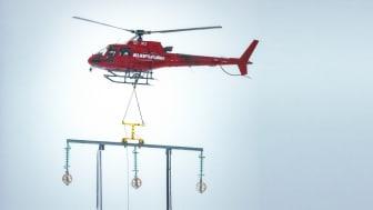 Med stor precision sätter helikopterpiloten ned regeln på stolptopparna.