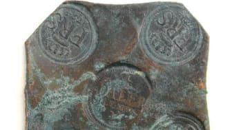 Ett av 21 kopparplåtmynt som en familj i Kristianstads kommun hittade på tomten. Mynten är från första hälften av 1700-talet och de är knappt tio centimeter breda. Foto: Länsstyrelsen Skåne (CCBY)
