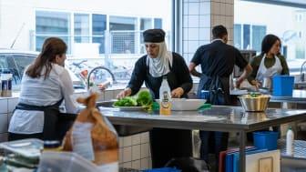 Kursister på flygtningeforløbet er i gang med at forberede mad til deres afslutningsmiddag.