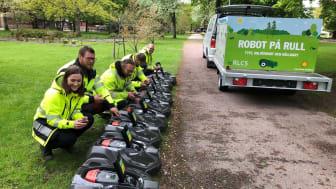Kommunens personal programmerar de nya robotgräsklipparna.