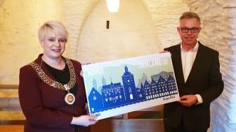 Ordfører Marte Mjøs Persen og frimerkedirektør Halvor Fasting viser fram jubileumsfrimerket for Bergen 950 år. Lanseringen skjedde i historiske Håkonshallen.