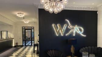 """Wallenstams logotyp finns i två versioner, namnlogotypen som består av myran centrerad ovanför ordmärket """"Wallenstam"""" samt W-logotypen som består av myran till höger om W, en  förkortning av Wallenstam."""