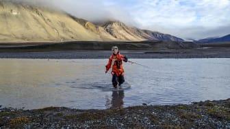 Forskar Pernilla Carlsson ved NIVA går triumferande i land frå Ebbaelva ved Petuniabukta, Svalbard, med ein prøvetakar for miljøgifter i handa. (Foto: Sverre Johansen)