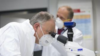 Ministerpräsident Stephan Weil beim Blick durch ein Mikroskop in einem Forschungslabor der DSMZ
