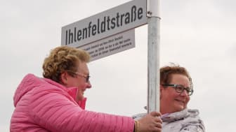 Tanja Kraas (links) und Kerstin Ihlenfeldt-Wulfes bei der Enthüllung des Schildes der Ihlenfeldtstraße, das ihre Eltern und DOYMA-Gründer Elisabeth und Hans-Ullrich Ihlenfeldt würdigt