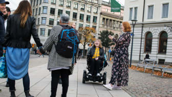 Ett gäng unga ser ut att ha träffats på en trottoar och stött på bekanta som stannat till för att prata.