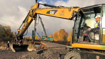 Teknik- och fastighetsnämndens ordförande, Henrik Lander (C), sitter bakom spakarna i grävmaskinen och tar det första symboliska spadtaget för en ny bro mellan Lamberget och Örsholmen.