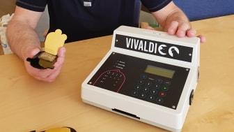 Mikael Kubista håller ett chip för analys av SARS-CoV-2 virus bredvid en prototyp av Pathpod