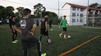 Geylang International's Gabriel Quak (in green) with the U18 players from Lakeside Family Services during the Epson Football Clinic at The Arena