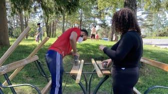 Yousef og Diana pusser benkeplanker.