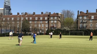 People playing cricket on an outdoor astro pitch in Southwark, with the Shard in the background
