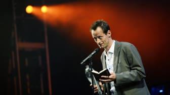 Årets Dramatiker 2016 går til Peter Asmussen for den dystre tableau-forestilling 'Soli Deo Gloria' på Betty Nansen Teatret. Dramatiker, instruktør og teaterleder Simon Boberg modtager her prisen.